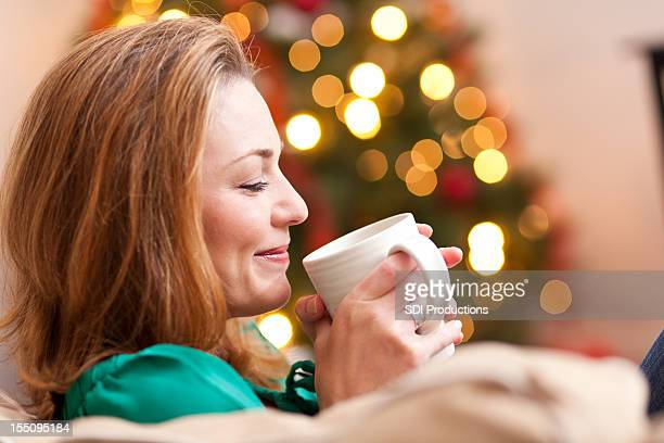 Relaxed young woman enjoying hot drink at Christmas time