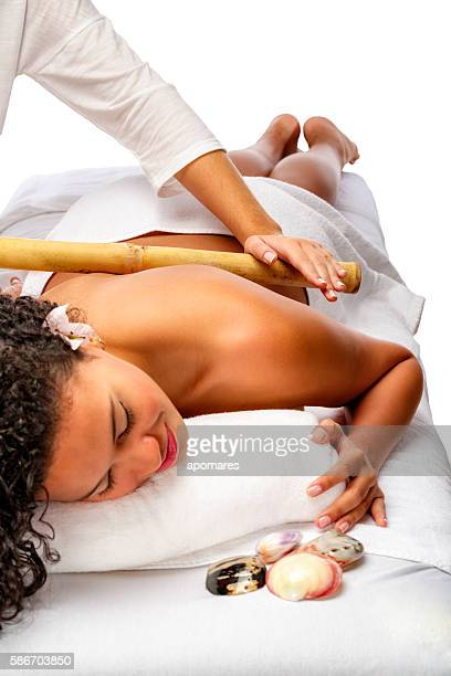 relaxed young woman getting bamboo massage therapy - bamboo - fotografias e filmes do acervo