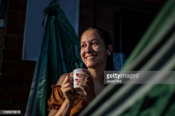 relaxed young woman having a cup of coffee - royal person stock pictures, royalty-free photos & images