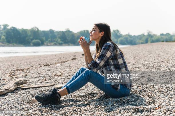 relaxed young woman holding a mug sitting at the riverside - チェックシャツ ストックフォトと画像