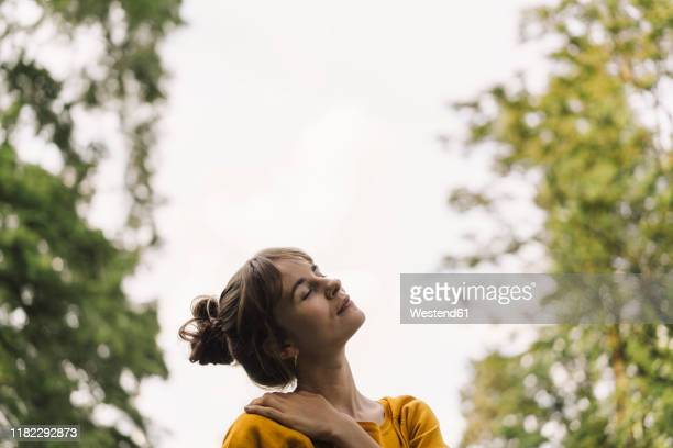 relaxed young woman in a park - mindfulness stock pictures, royalty-free photos & images