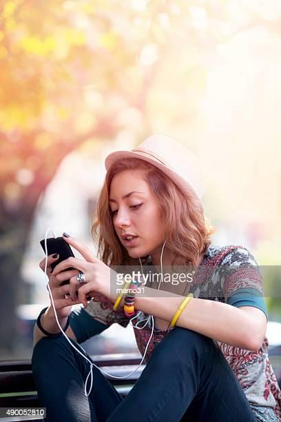 Jeune femme décontractée, écouter de la musique dans le parc