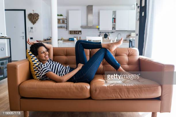 relaxed young woman lying on couch at home - resting stock pictures, royalty-free photos & images