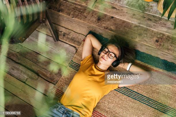 relaxed young woman lying on the floor at home listening to music - hands behind head stock pictures, royalty-free photos & images