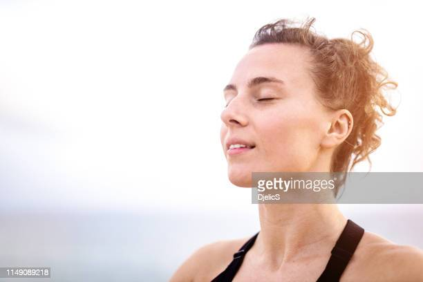 relaxed young woman meditating outdoors by the sea head close up. - gente serena foto e immagini stock