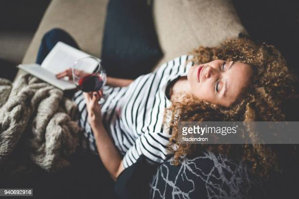 relaxed young woman reading a book - serene people stock pictures, royalty-free photos & images