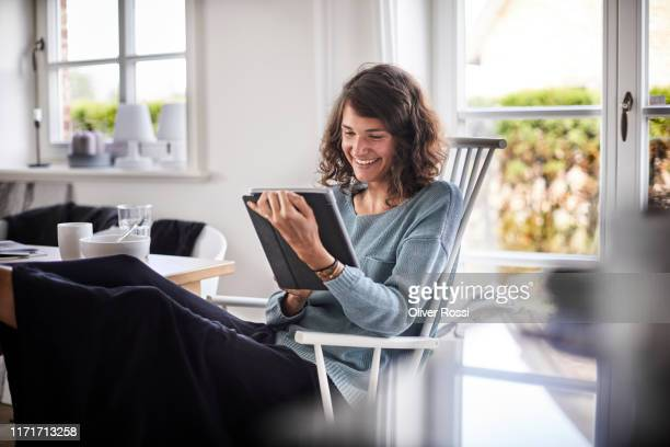 relaxed young woman sitting at table using tablet - satisfaction stock pictures, royalty-free photos & images