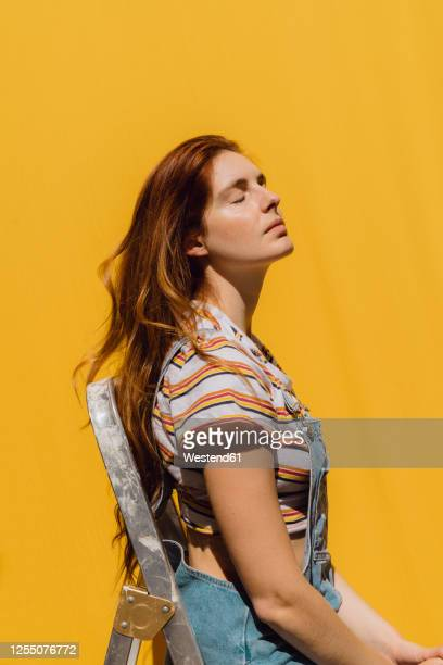 relaxed young woman sitting on ladder against yellow wall - 頭をそらす ストックフォトと画像