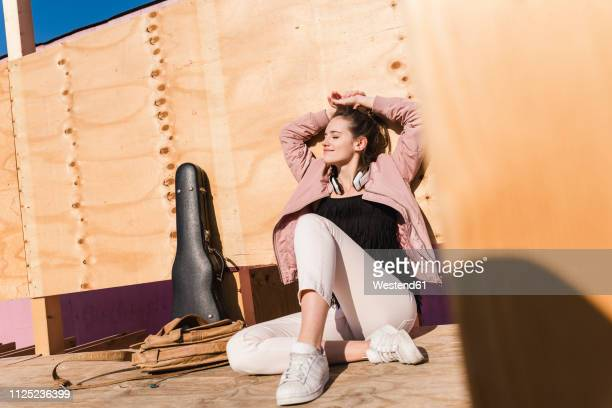 relaxed young woman sitting on platform next to guitar case and bag - pause machen stock-fotos und bilder