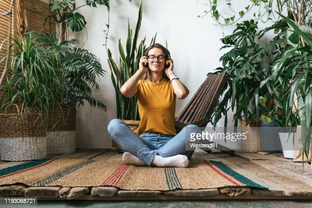 relaxed young woman sitting on the floor at home listening to music - lazer imagens e fotografias de stock