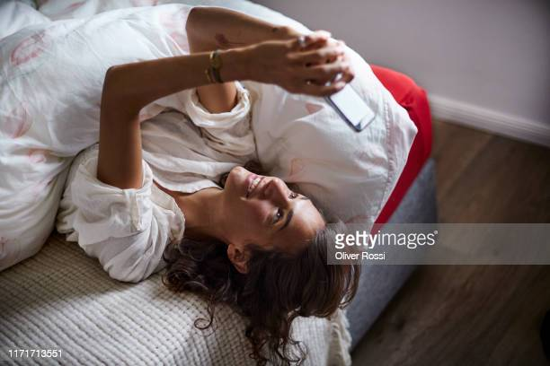 relaxed young woman using cell phone in bed - bed stock pictures, royalty-free photos & images