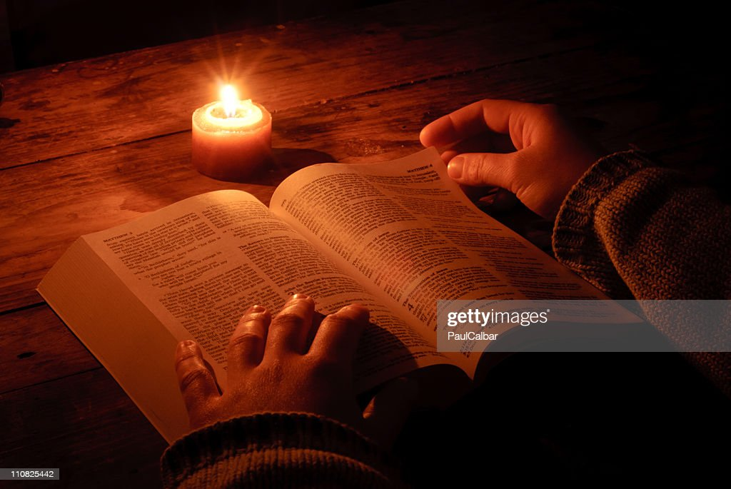 Relaxing and reading bible by candlelight at night : Stock Photo