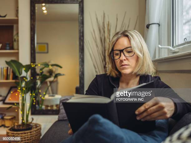 ontspannen thuis - alleen mid volwassen vrouwen stockfoto's en -beelden