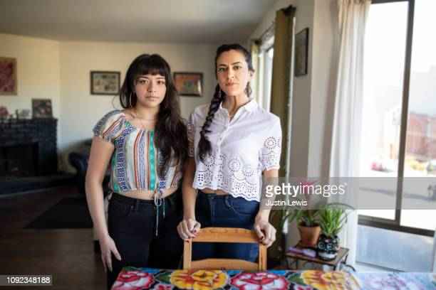 relaxing at home, two millennial latina women stand near dining table - sugar skull stock photos and pictures