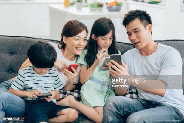 ワイヤレス テクノロジの自宅でリラックス - 子供2人の家庭 ストックフォトと画像