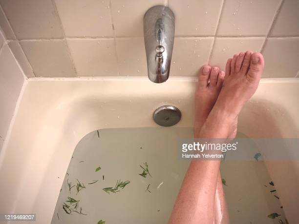 relaxing bath showing woman's ankles crossed soaking in herbal bath - massage tantrique photos et images de collection