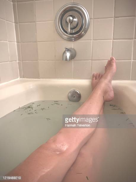 relaxing bath showing woman's legs crossed - massage tantrique photos et images de collection