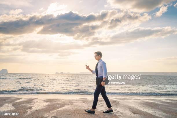 Entspannende Geschäftsmann mit Laptop und Smartphone am Strand