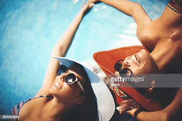 relaxing by pool side. - women sunbathing pool stock photos and pictures