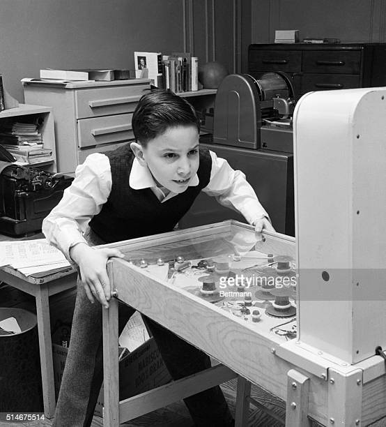Relaxing from his scientific endeavor 10yearold Robert Strom tries his hand at a pinball machine in the Bronx NY The intricacies of the machine pose...
