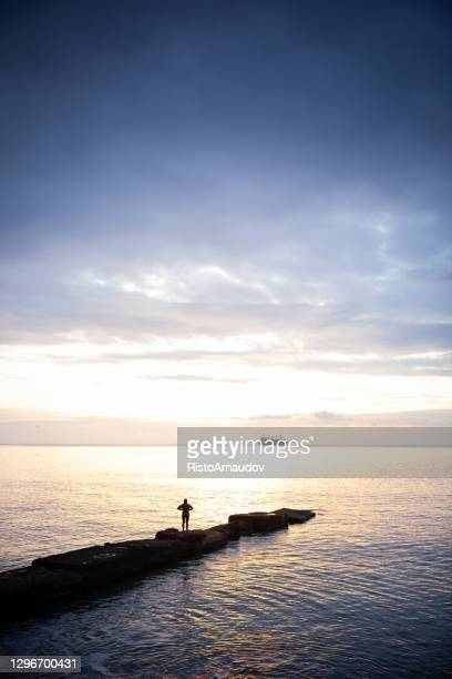 relaxing in beautiful landscape on pier at sunset - human back stock pictures, royalty-free photos & images