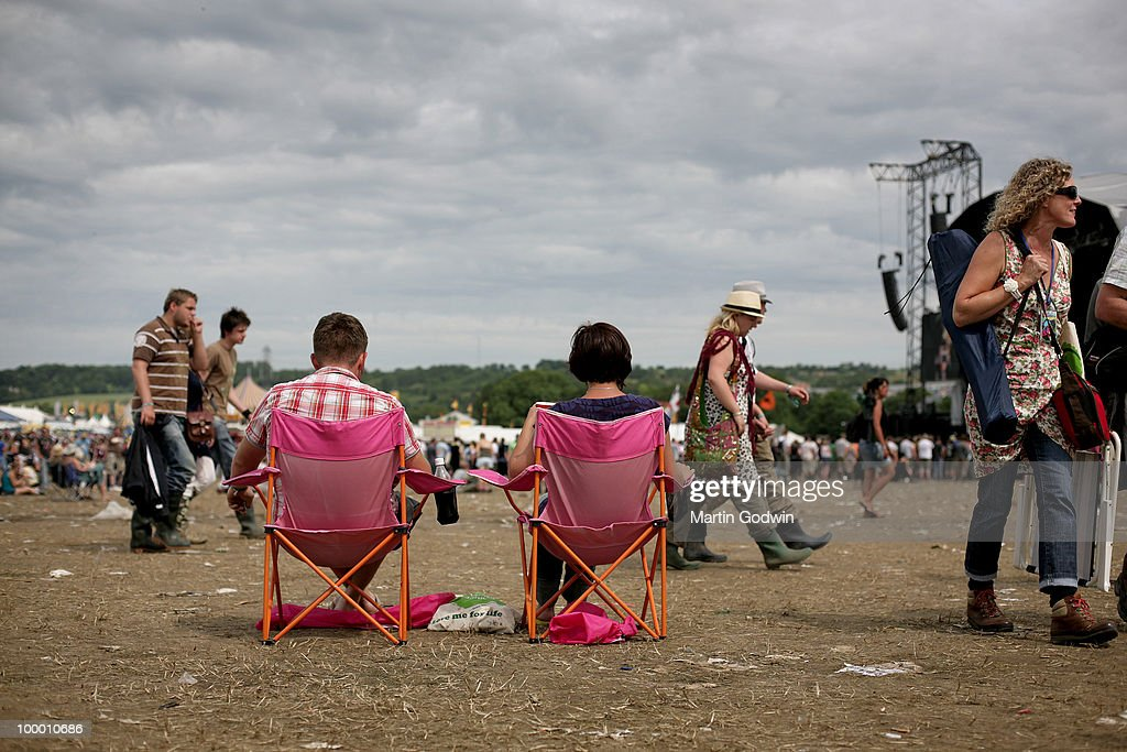 Relaxing in matching pink and orange camping chairs on Sunday morning at Glastonbury, 28th June 2009.
