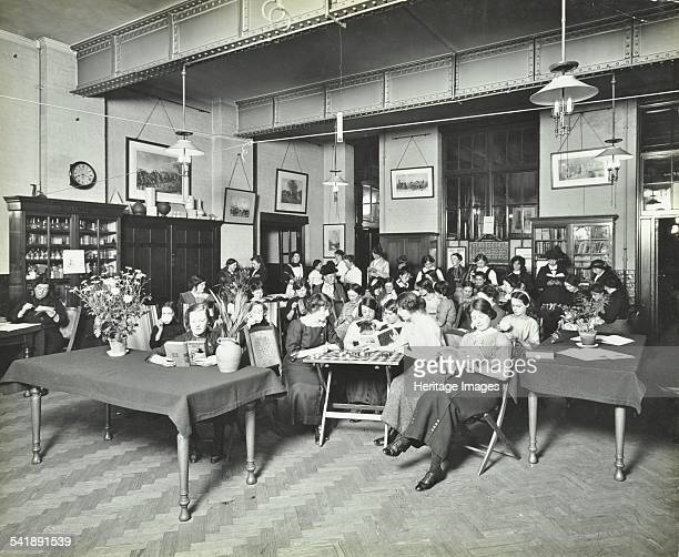 Relaxing in the Social Hall Cosway Street Evening Institute for Women London 1914 Women and girls reading drinking tea and playing draughts Artist...