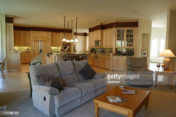 relaxing living room with grey loveseat near kitchen - reclining chair stock photos and pictures
