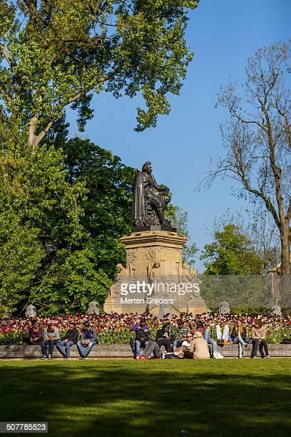 relaxing people around joost van vondel statue - merten snijders stock-fotos und bilder
