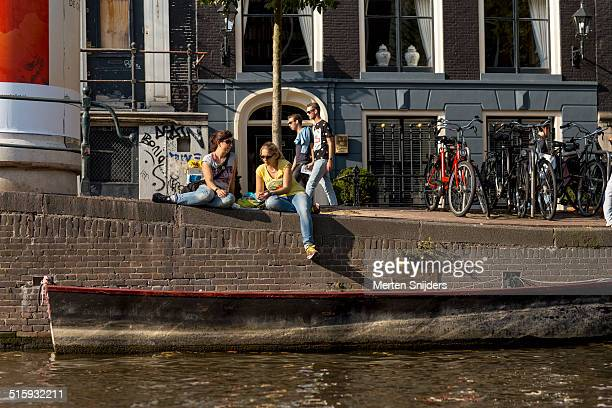 relaxing people dangling their feet at canal - merten snijders - fotografias e filmes do acervo