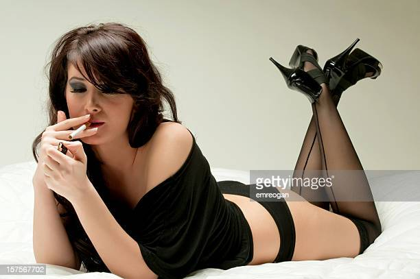 relaxing - beautiful women smoking cigarettes stock photos and pictures