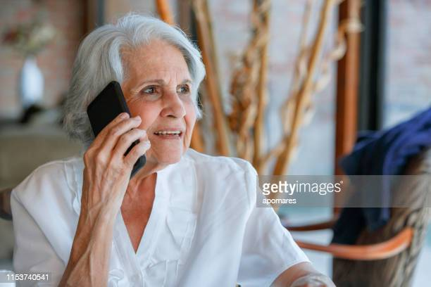 relaxing senior woman using mobile phone while sitting in living room - spanish and portuguese ethnicity stock pictures, royalty-free photos & images
