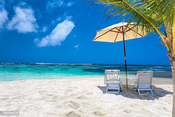 isla caribe tropical playa relajante sombrilla y sillas - paisajes de bahamas fotografías e imágenes de stock