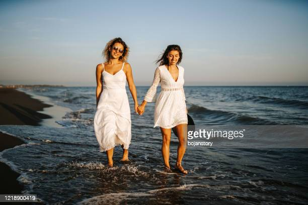 relaxing walk on beach - white dress stock pictures, royalty-free photos & images