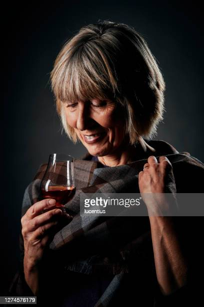 relaxing with a small glass of whisky - whisky stock pictures, royalty-free photos & images