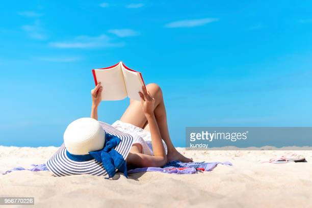 relaxing woman laying to read a book on the beach with blue sky in sunny day summer. happy travel and vacation times. - sunbathing stock pictures, royalty-free photos & images