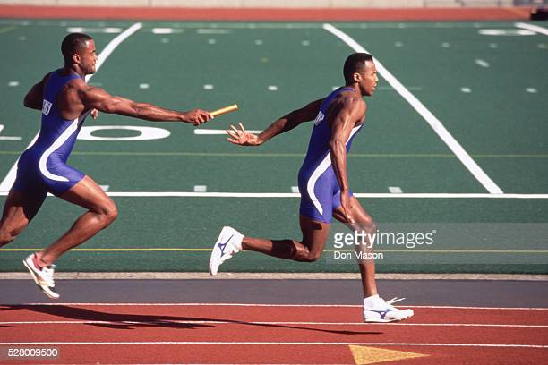 relay racers handing-off baton - relay stock pictures, royalty-free photos & images