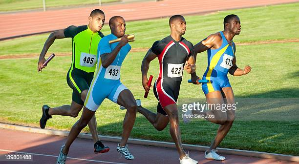 relay racers running on track in race - relay stock photos and pictures