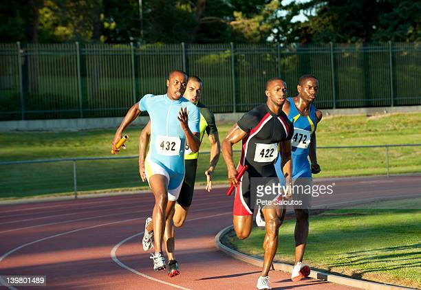 relay racers running on track in race - 陸上競技大会 ストックフォトと画像