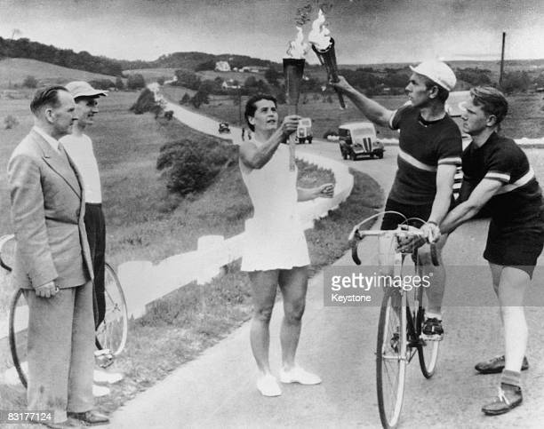 A relay runner passes the Olympic flame to a cyclist on the road between Aalborg and Randers in Jutland en route to the opening ceremony of the...