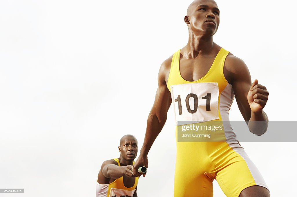 Relay Runner Passing a Baton to a Determined Looking Team Mate : Stock Photo