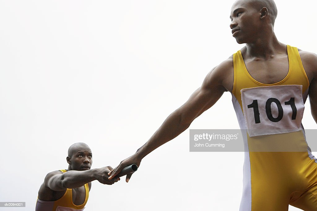 Relay Runner Passing a Baton to His Team Mate : Stock Photo