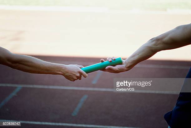 Relay runners exchanging baton, close-up