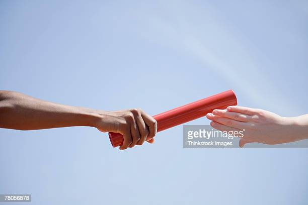 Relay runners' hands passing baton