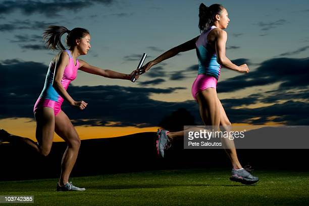 relay runners passing baton in competition - passing sport stock pictures, royalty-free photos & images