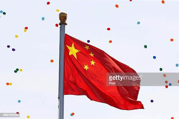 Released balloons fly around the China national flag during a military parade marking the 70th Anniversary of the 'Victory of Chinese People's...