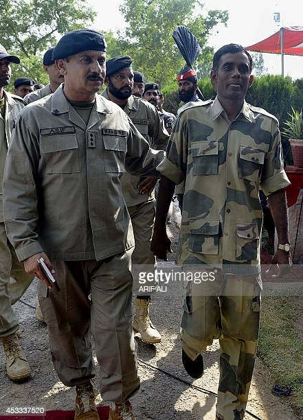 Released Indian border guard Satyasheel Yadav walks with Pakistani officials prior to crossing over to India at the border post Anayat Hussain...