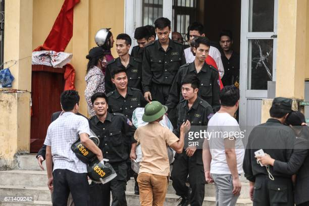 Released policemen walk out from the communal house at Dong Tam commune My Duc district in Hanoi on April 22 2017 More than a dozen police and...