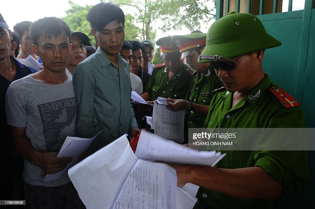 Released prisoners (L) are identified by policemen at a gate before they leave the Hoang Tien prison in Chi Linh district, northern province of Hai Duong on August 30, 2013. Vietnam will free more than 15,000 convicts to mark its independence day celebrations, the president's office said on August 29, in a major amnesty that excludes prominent political prisoners. AFP PHOTO/HOANG DINH Nam