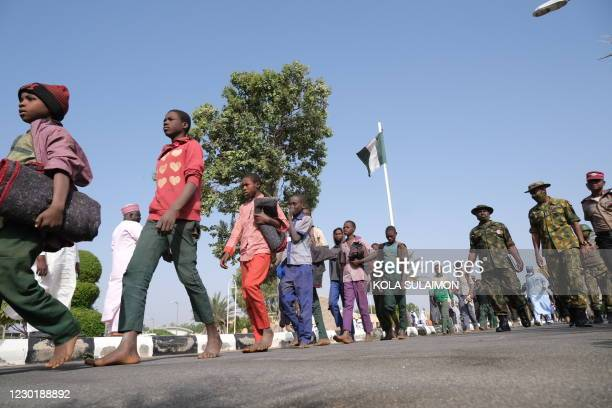 Released students from the Government Science Secondary school, in Kankara, in northwestern Katsina State, Nigeria are led into the Government House...